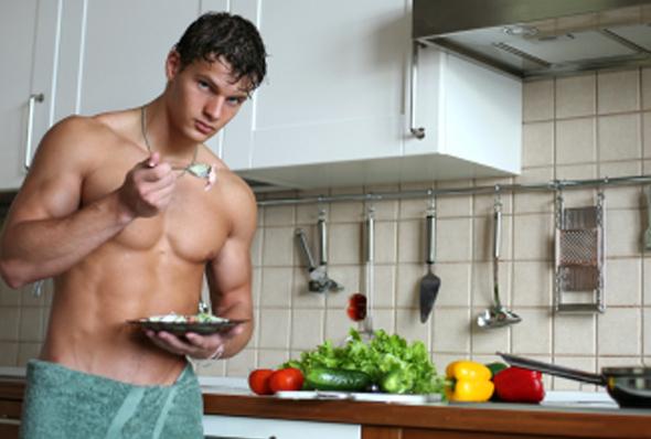 натренированный молодой человек ест после упражнений