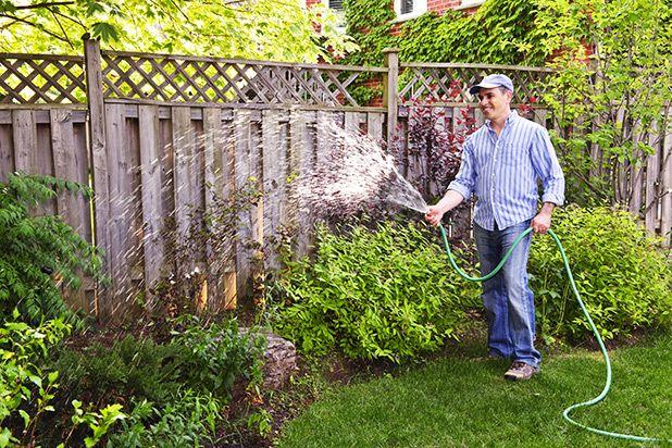 парень поливает огород из шланга