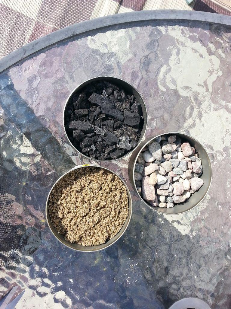 Прямо поверх сетки закладываем в банки: тщательно промытый гравий в первую, промытый песок во вторую и уголь в третью