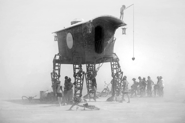 ежегодный сюрреалистический фестиваль «Горящий человек» (Burning Man): мальчик на крыше старинной повозки-дома удит любовь