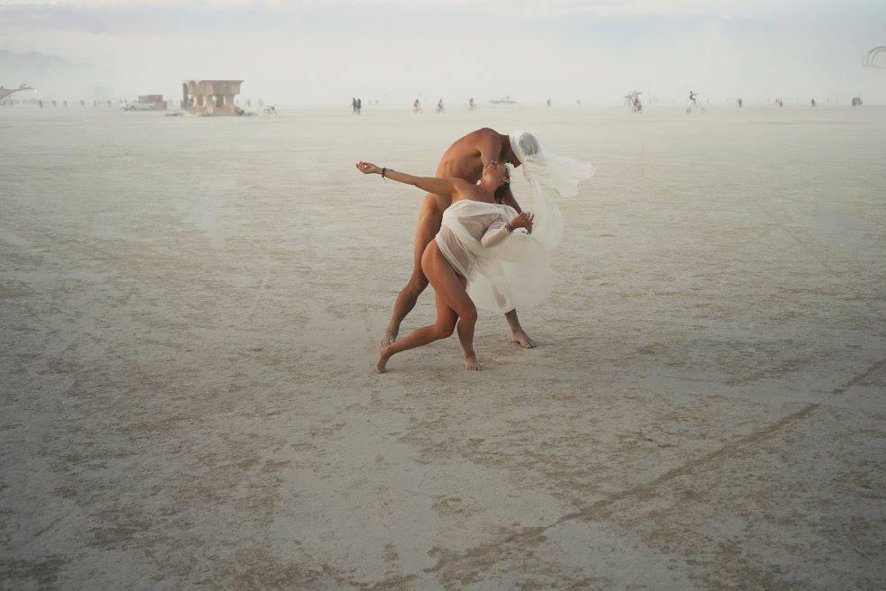 ежегодный сюрреалистический фестиваль «Горящий человек» (Burning Man): танцующая обнаженная пара в платках