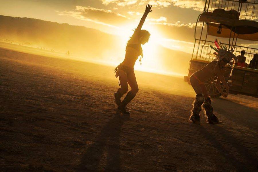 ежегодный сюрреалистический фестиваль «Горящий человек» (Burning Man): девушки, танцующие индейский танец на закате