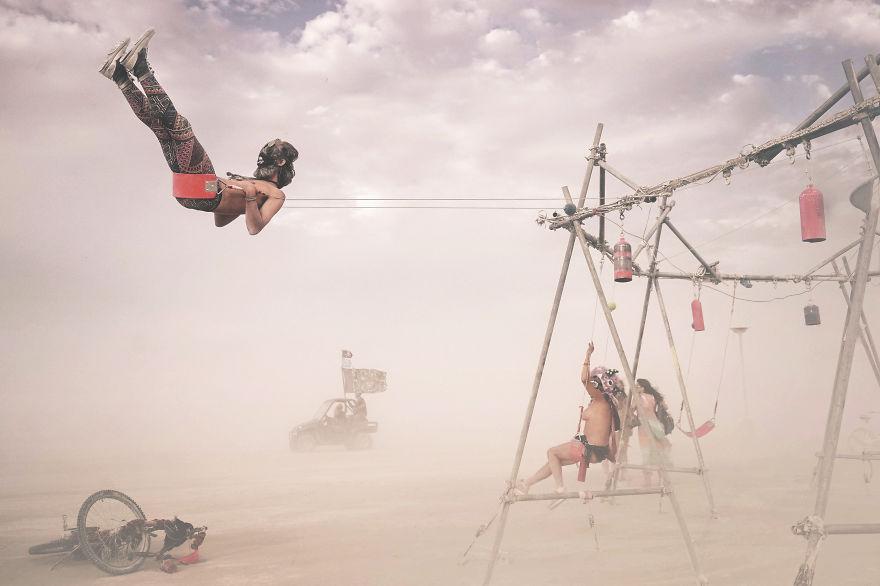 ежегодный сюрреалистический фестиваль «Горящий человек» (Burning Man): полуобнаженные девушки на качелях