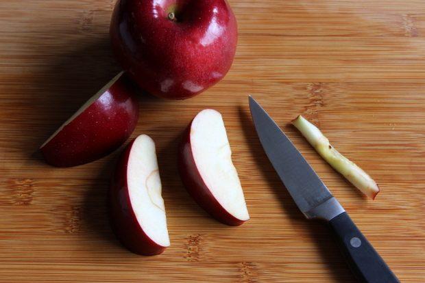 На острой грани каждой дольки сделайте прямой разрез, полностью срезая семена и пленку около них в центре яблока