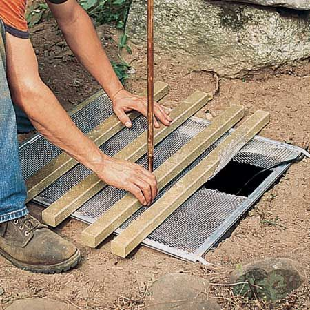 Ножовкой отрезаем от композитного материала несколько секций, достаточно длинных, чтобы надежно положить их между краями вырытой ямы на сетку поперек ямы