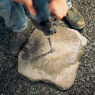 Кладем камни по одному на мягкую землю или гравий. Сверлим камни на метках насквозь.