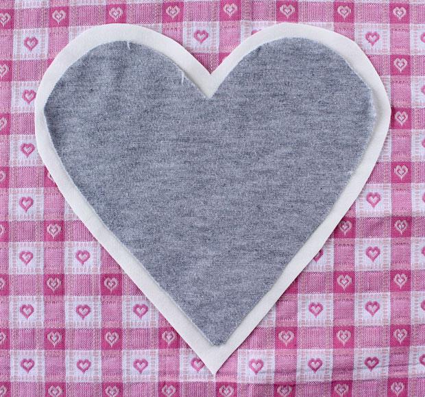 По шаблону же вырежьте почти такое же сердце из другого куска ткани (более плотной, чем материал футболки, но мягкой), но прибавив к шаблону со всех сторон – по всему периметру - по 1,3 см