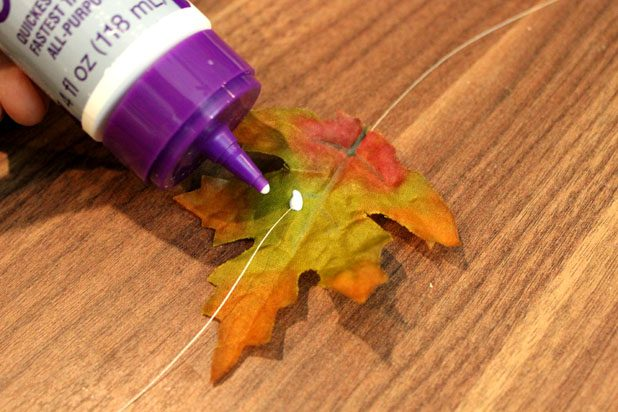 В том месте, где нитка соприкасается с каждым листочком, наносите снизу (под листом) каплю подходящего клея