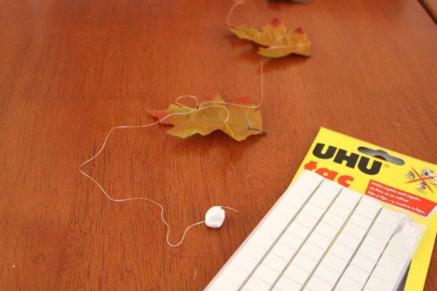 Мастика отщипывается от бруска, скатывается в шарик и в него помещается верхний кончик одной нитки с листьями