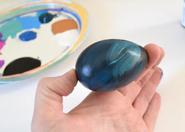 Пока краска на яйце все еще влажная, окуните кисть в черную краску и сделайте тут-там кистью на яйце завихрения