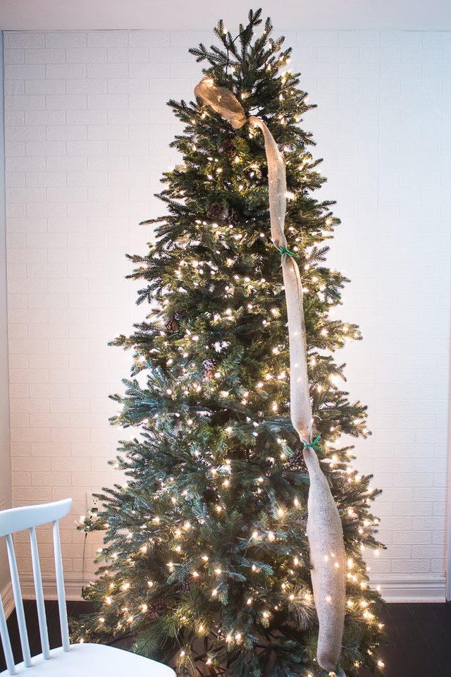 Начиная с верхушки елки, кониками проволоки приматываем начало гирлянды на любую ветку елки сзади