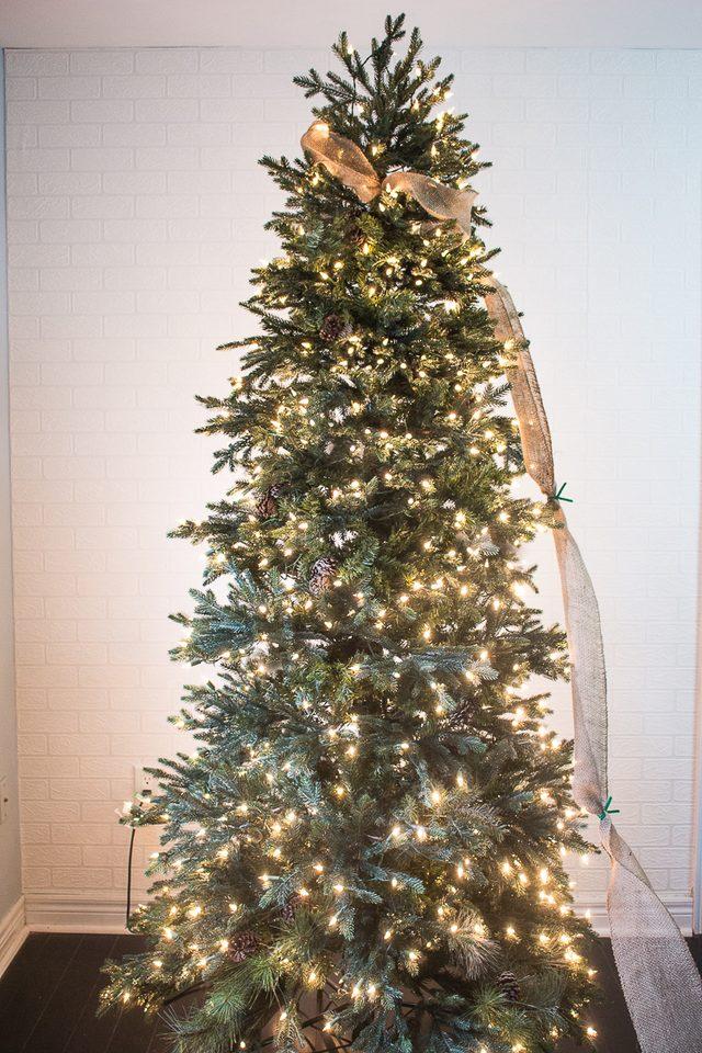 Теперь постепенно ведите гирлянду вокруг елки по не растянутой (но и не плотной) спирали, и привязывайте ленту к новым веткам