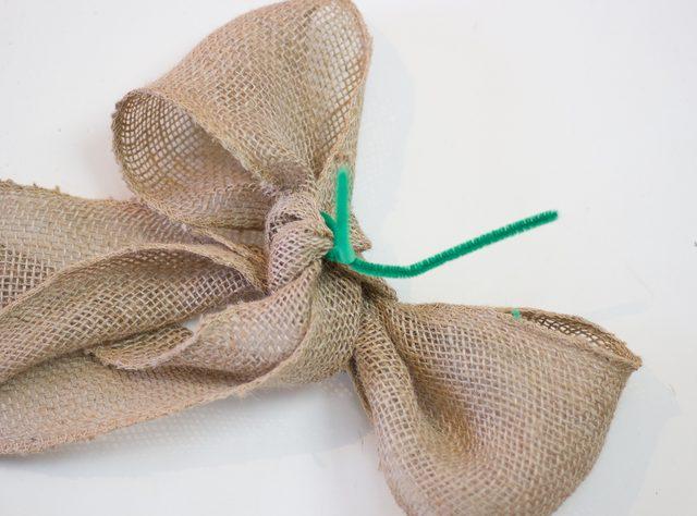 Для макушки елки завяжите из куска широкой ленты крупный бант с длинными кончиками. В бант проденьте сзади проволоку и зафиксируйте первый на самой верхней ветке елки