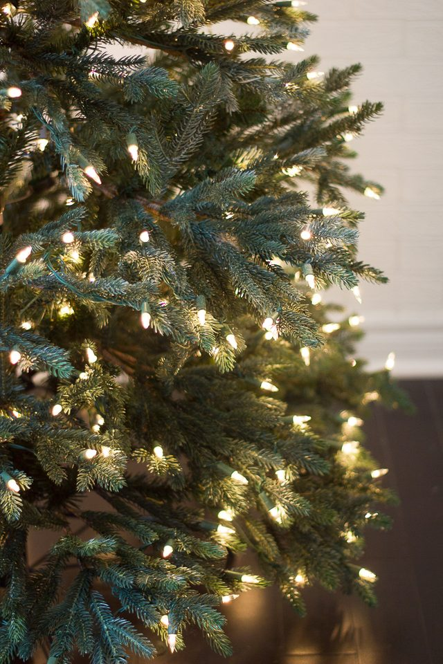 Сначала вешаем несколько вглубь елки гирлянды с фонариками – поверх лент вы уже ничего не сможете повесить, кроме елочных игрушек