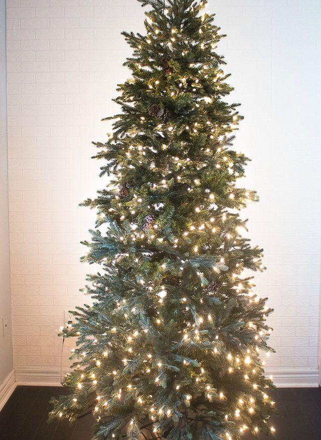 После лампочек в глубине – у основы – елки повязываем отдельные зеленые ветки при помощи кусков гирлянды