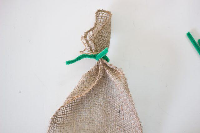 Кончик первой гирлянды оборачиваем проволокой, оставляя достаточно длинные кончики проволоки свободными – за них вы будете цеплять гирлянду на елку