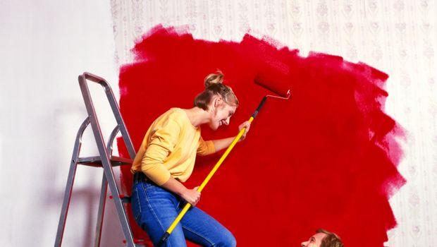 Как грамотно ввести красный в интерьер. Девушка красит стену.