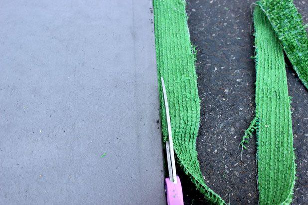 Используя края резинового мата как ведущие, обрежьте зеленое покрытие ровно по этим краям
