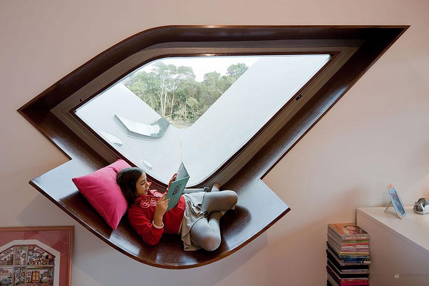 Уголок для чтения в виде увеличенного подоконника, повторяющего необычную форму окна