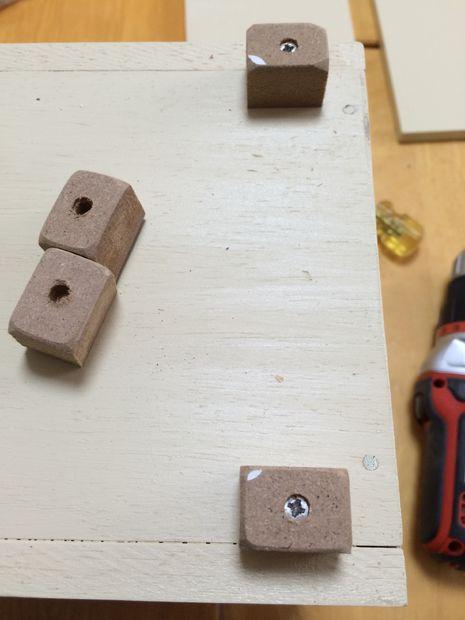С отступами от краев, как показано здесь, привинтите к дну коробки толстые ножки из прочного, но относительно мягкого материала
