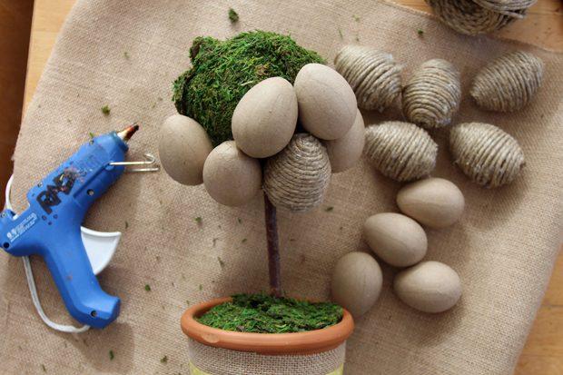 Начиная снизу, клейте яйца на шарик в мхе