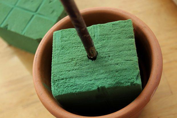 Пеноматериал поместите в горшок, по центру первого вставьте до дна горшка вашу палочку, которая будет имитировать ствол дерева