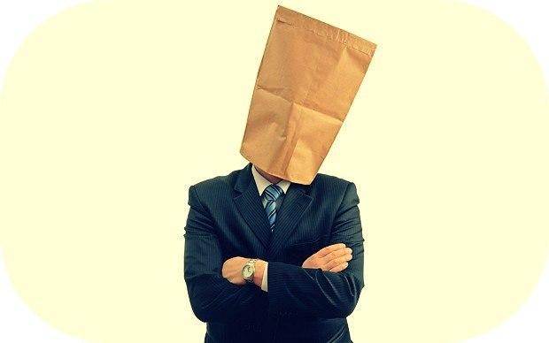 мужчина в костюме с бумажным пакетом на голове