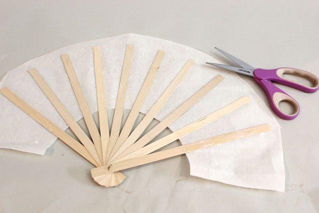 С отступом вверх от палочек в 2,5 см обрежьте бумагу полукругом