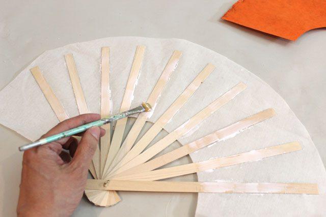 Наносим клей на вторую сторону палочек до места, где заканчивается белая бумага