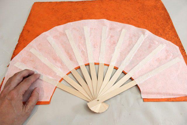 Накладываем декоративную деталь тыльной стороной на палочки таким образом, чтобы снизу ее полукруг заходил за границу белой бумаги вниз примерно на 0,6 см