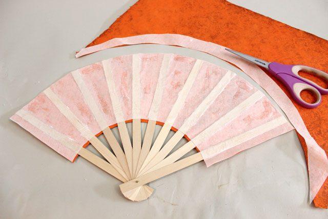 используя вершины палочек в качестве направляющих, обрежьте оба слоя бумаги на веере сверху ровным полукругом