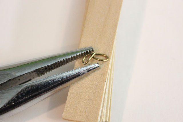 Плоскогубцами закрутите кончик булавки в спиральный завиток очень плотно к стопке палочек