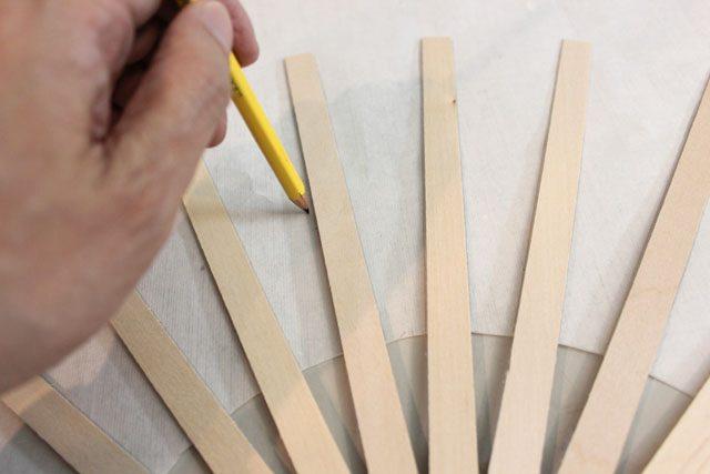 Аккуратно прижимая палочки пальцем, карандашом обрисовываем по бокам их точное расположение на бумаге