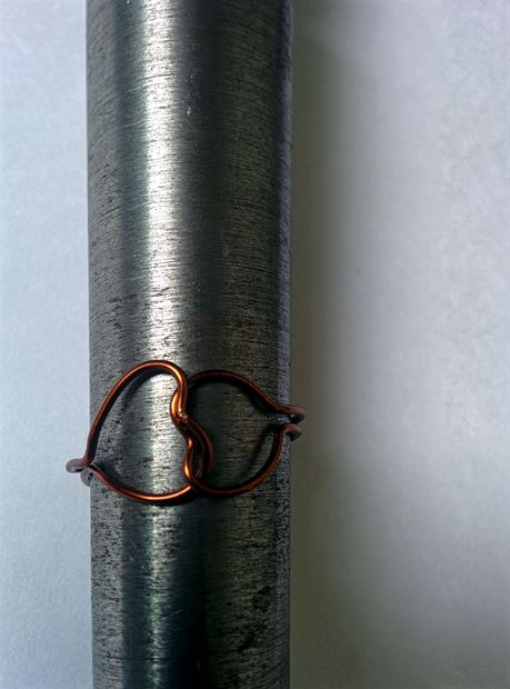 наденьте кольцо на крупный цилиндрический предмет и, прижимая пальцами со всех сторон, получите из сердец и кончиков проволоки идеальный круг – форму, собственно, кольца
