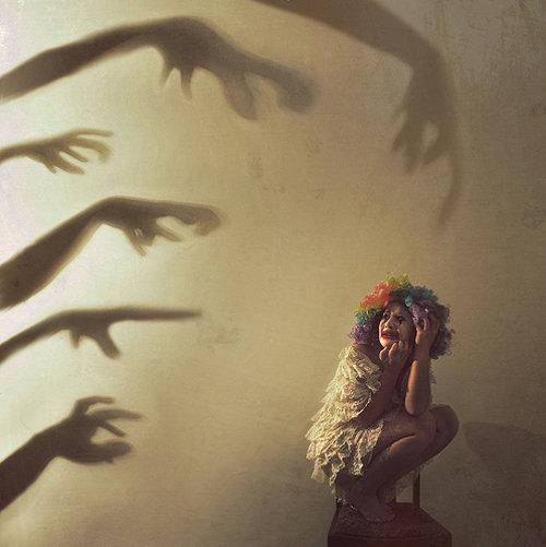 руки-тени тянутся к девушке в карнавальном костюме