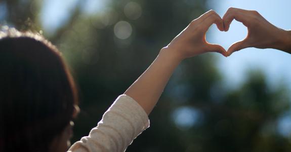 девушка складывает сердечко из пальцев