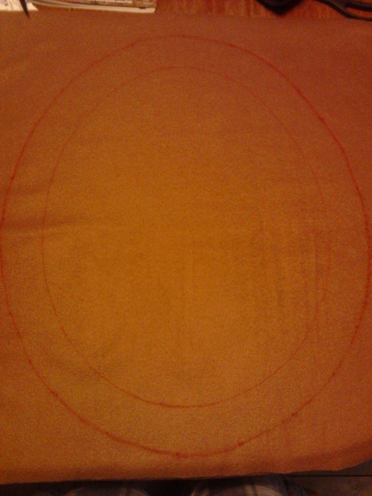 Кладем овал на коричневый флис и пунктиром «обводим», но с отступом в 7,5 см от картонного шаблона