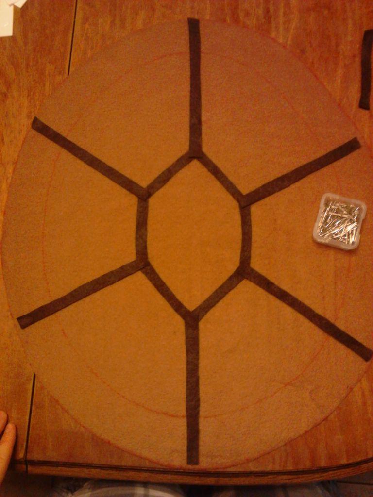 На овале большего размера из ткани выкладываем и закалываем узор из таких же полосок, как в п. 8. Точно также пришиваем эти полоски на машинке.