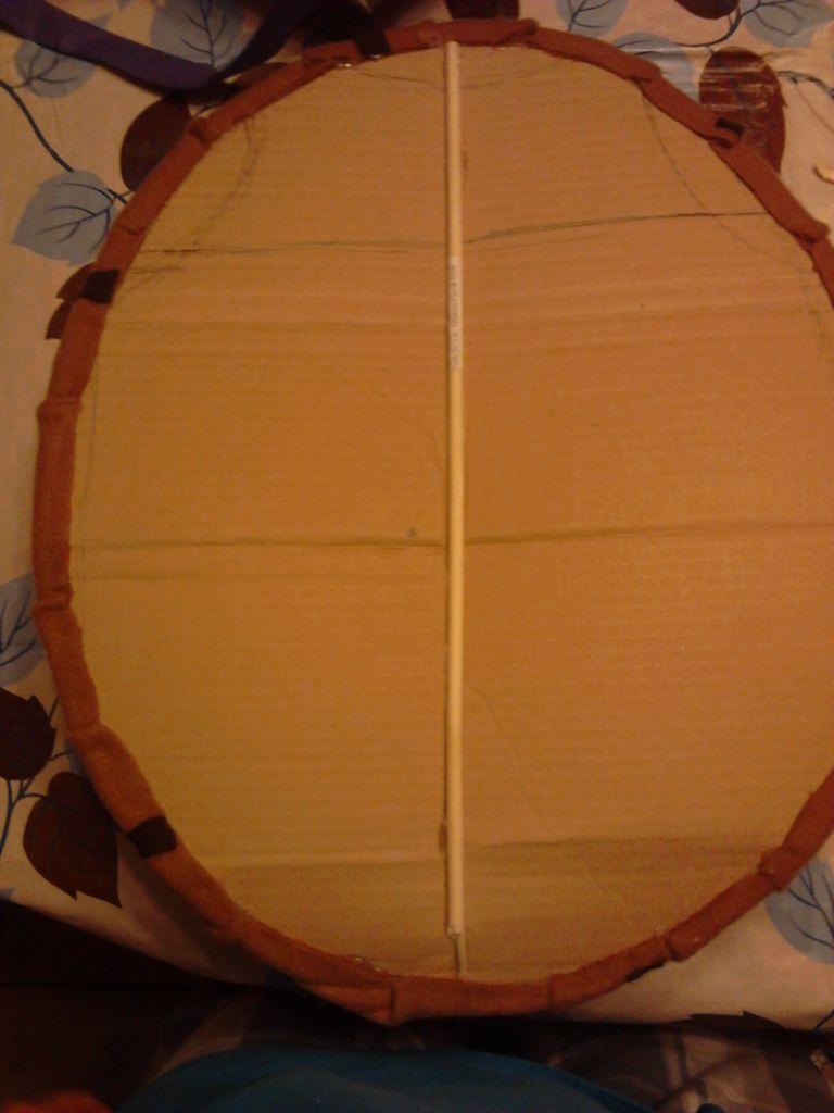 Если в процессе работы вы обнаружили, что картон недостаточно прочный, возьмите тонкую деревянную досочку и приклейте ее по длине панциря ровно посередине, чтобы укрепить данную деталь костюма