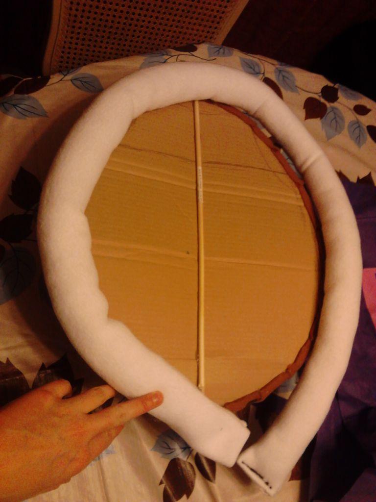 Горячим клеем крепим эту трубу по периметру панциря – к картону и ткани складками