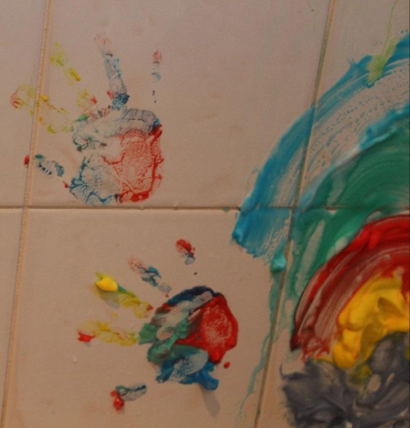 Девочка ставит специальными красками отпечатки рук на кафеле в ванной