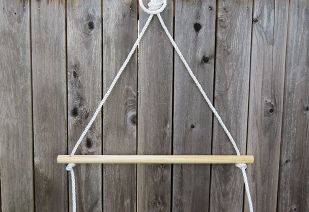 проденьте по одному кончику висящей веревки в каждое отверстие на концах палки - слева и справа