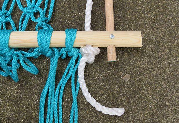 Начиная с нижней части рамки гамака-кресла, протяните по одному концу каждой веревки через свободные отверстия в палке справа и слева и завяжите под палкой по свободному узлу