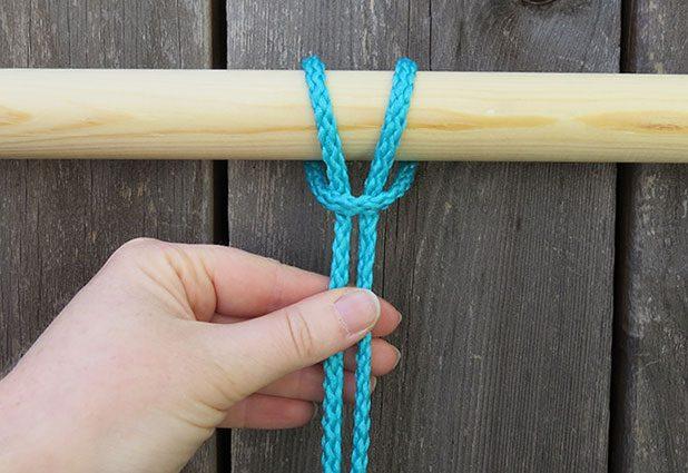 Возьмите первый кусок шнура, сложите ровно пополам и оберните петлю вокруг верхней палочки (большего диаметра) рамки – сверху назад и вниз. Через петлю снизу протяните кончики этого же шнура и затяните.