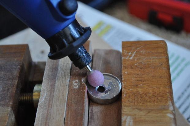 выбрав подходящую зернистость шлифовальной насадки, просуньте насадку в одно из двух проделанных более крупным сверлом отверстий