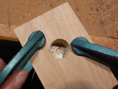 Зажмите тисками монету между деревяшкой с отверстием сверху и нижним слоем дерева и закрепите тисками же всю эту конструкцию на рабочей поверхности
