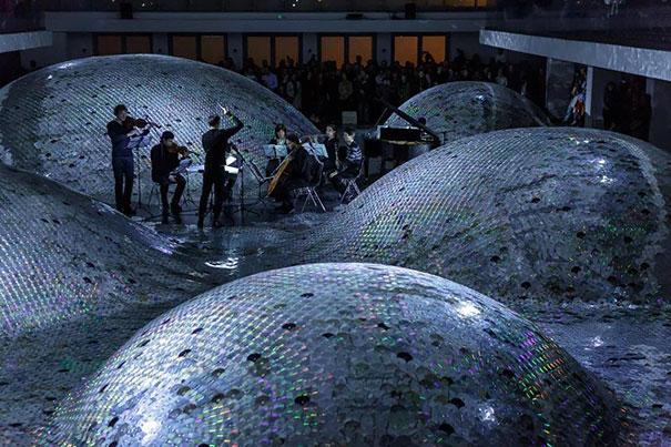 креативно использовать ненужные CD-диски: инсталляция в виде волн из дисков в галерее в Париже ночью - концерт