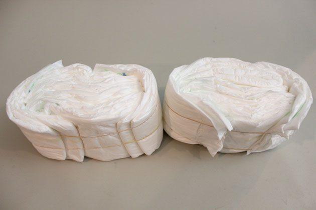 Для подушечки в коляску стопкой сложите 10 подгузников, стоящих вертикально. Еще 2 подгузника оберните вокруг 2-х концов стопки, чтобы получить овальную форму.