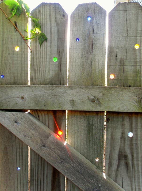 теклянными шариками можно изумительно украсить деревянный забор на даче, и тогда в солнечные дни ваш двор будет играть всеми оттенками радуги