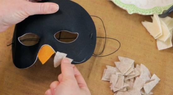 Продолжайте обклеивать нижний контур маски, но теперь «перья» клеим не с изнанки, а прямо поверх маски